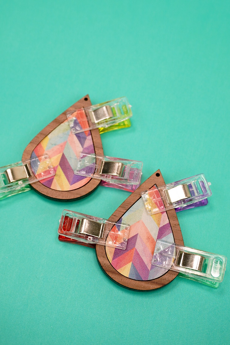 Wood earrings with colorful cork inlay and sewing clamps around edges