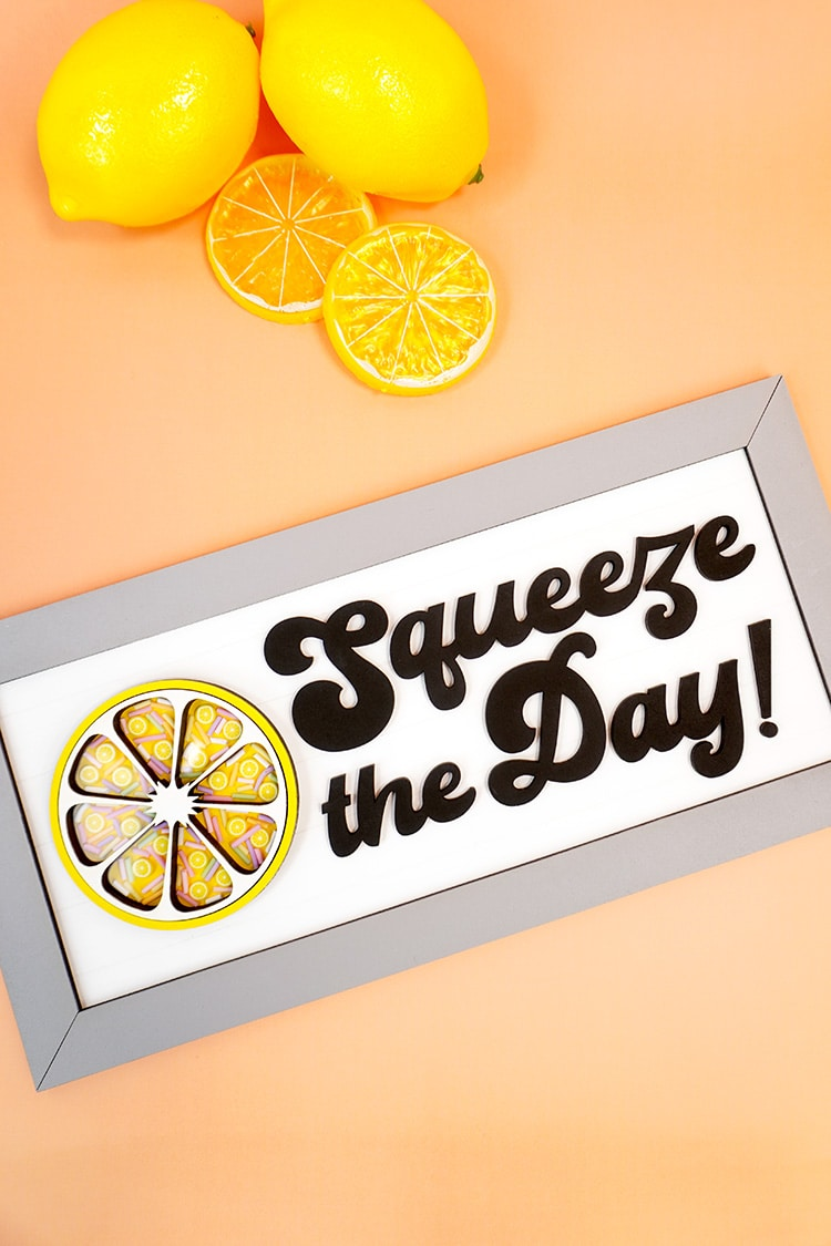 Squeeze the Day Lemon Sign on orange background with lemons