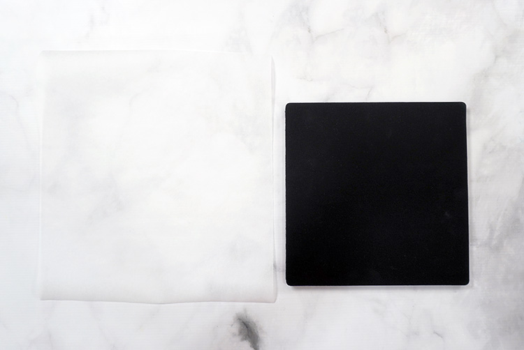 Heat resistant mat and sheet of butcher paper on marble background