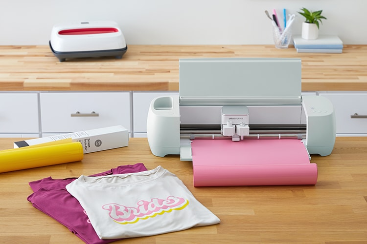 "Cricut Explore 3 on desktop with pink vinyl and ""bride"" shirt"