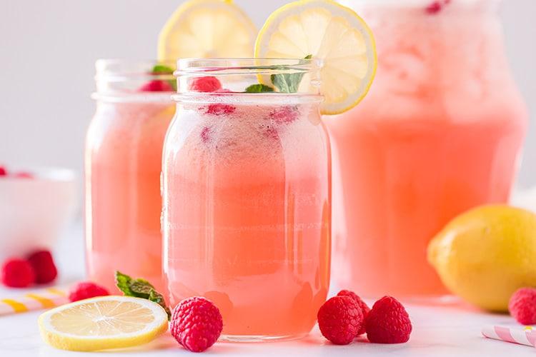 Two mason jar glasses of homemade raspberry lemonade with lemon wheels and fresh raspberries