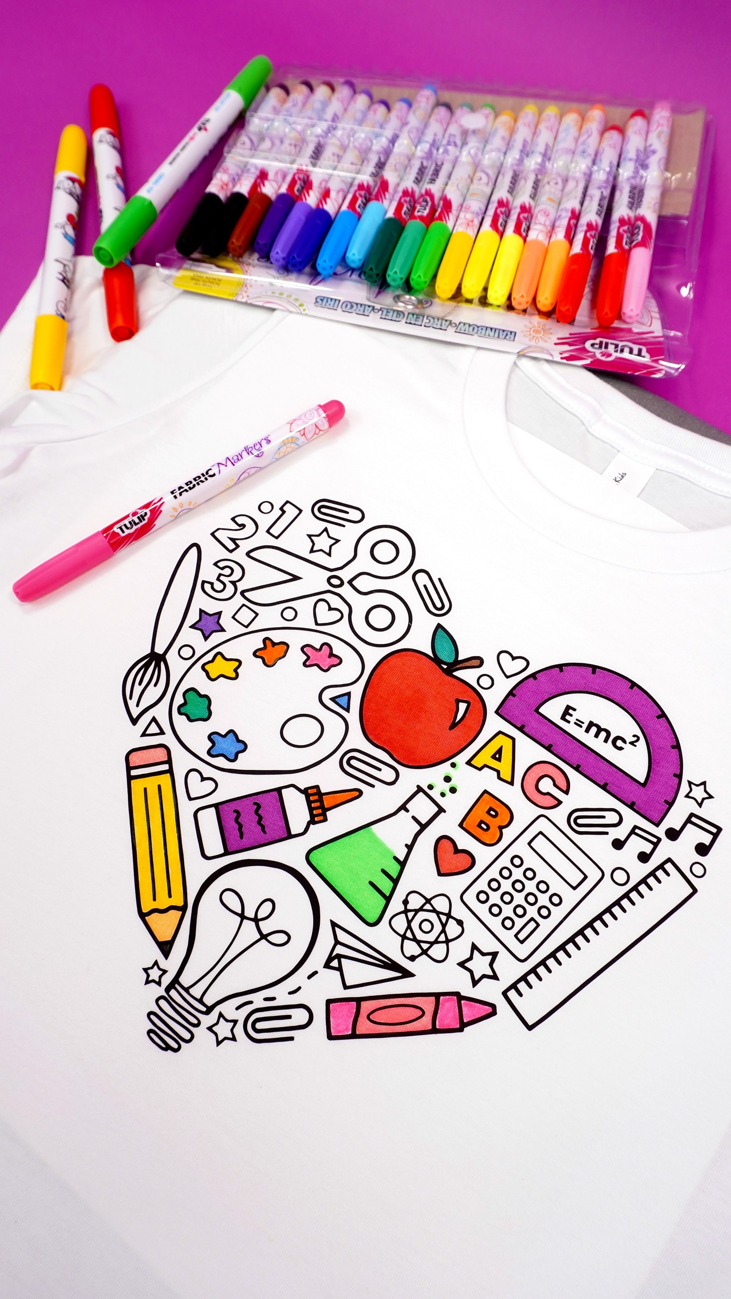 Close up view of partially colored back to school shirt with fabric markers on a purple background
