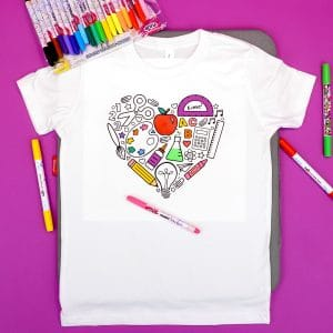 Partially completed coloring shirt with back to school themed design surrounded by fabric markers on purple background