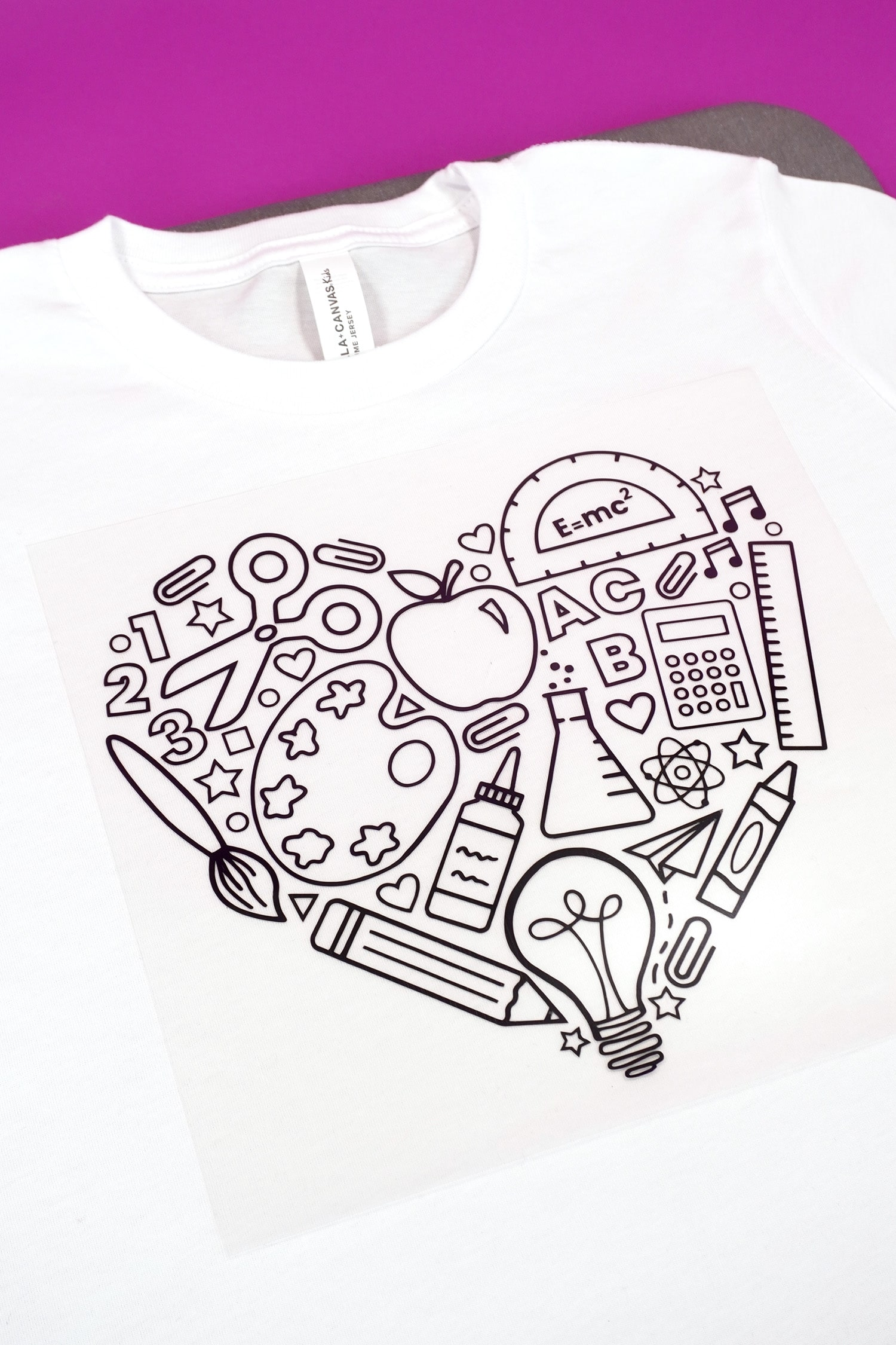Close up of back to school iron-on design on white shirt