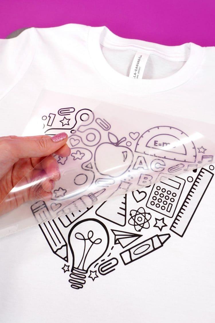 Hand peeling back heat transfer vinyl backing from shirt