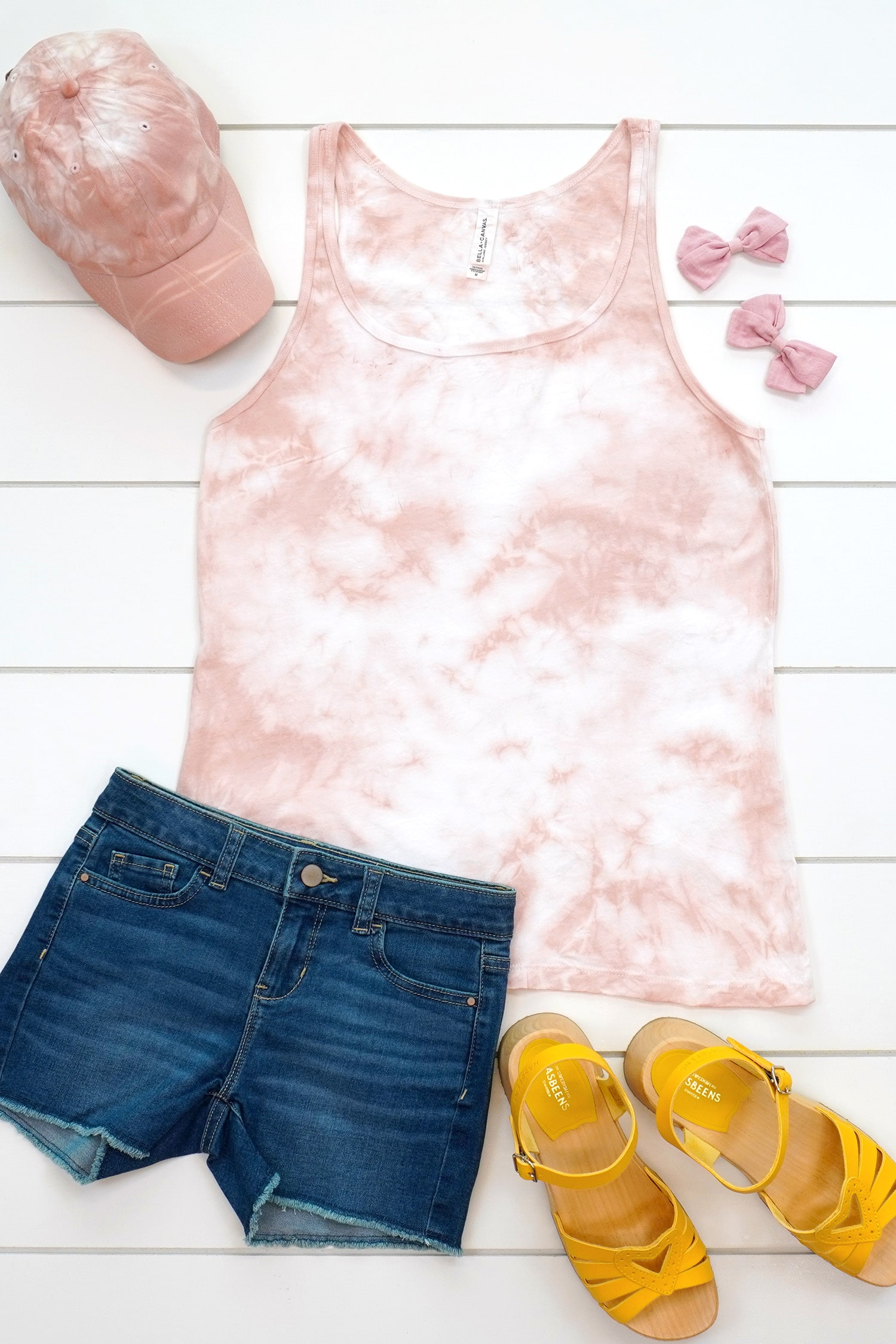 Blush pink tie-dye tank top and baseball hat made with avocado dye staged with an outfit and flowers on a white background