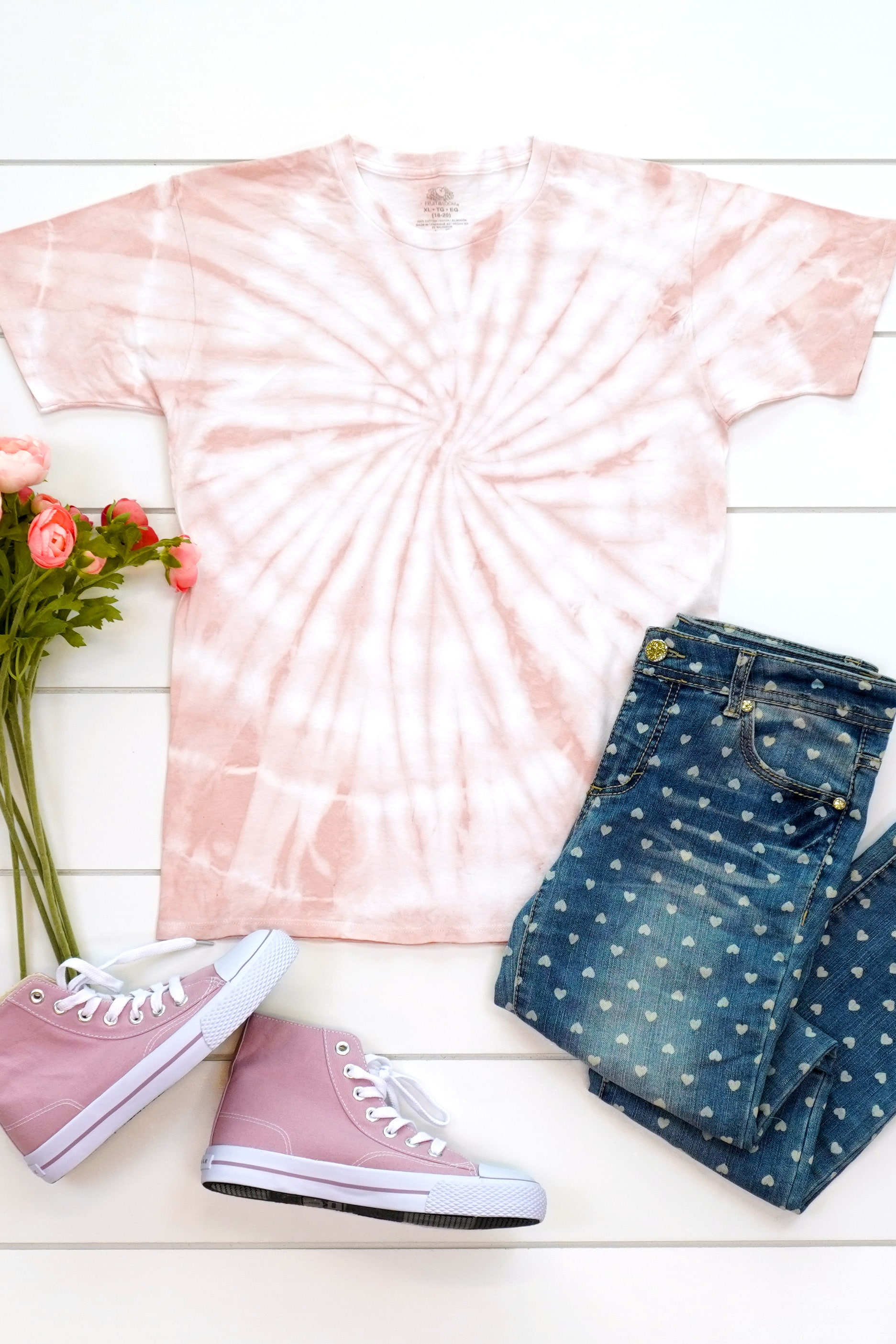 Blush pink spiral tie-dyed shirt made with avocado dye staged with an outfit and flowers on a white background