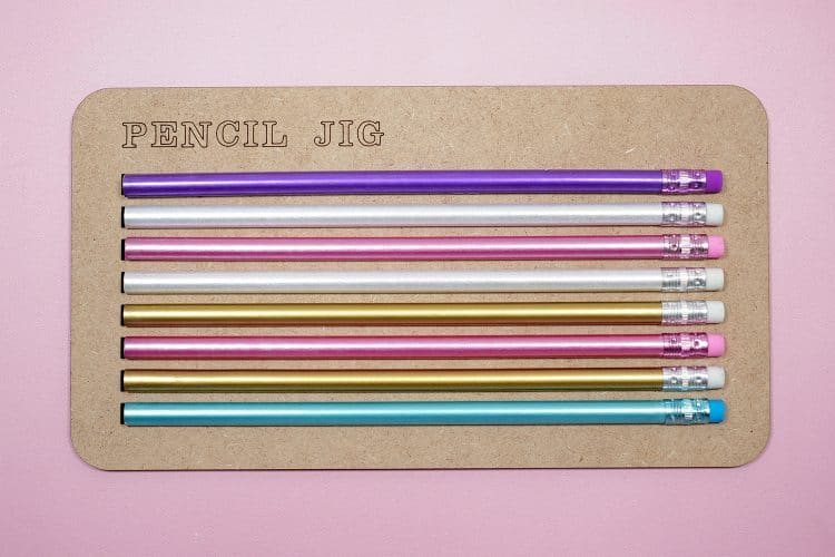 Colorful pencils in a pencil jig on a pink background