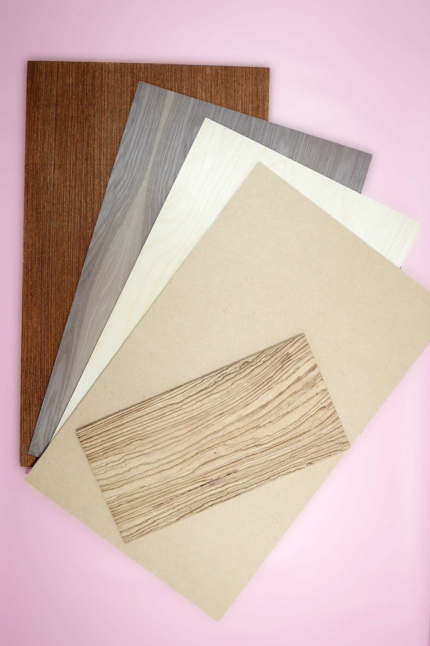 Five different types of wood sheets on a pink background