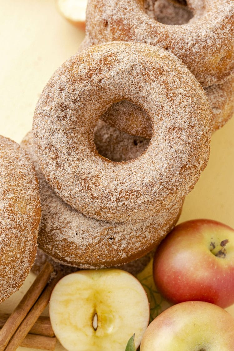 Apple cider donuts with cinnamon sugar topping on yellow background with apples