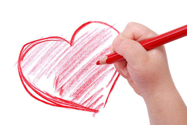 Child's hand with red pencil drawing a heart