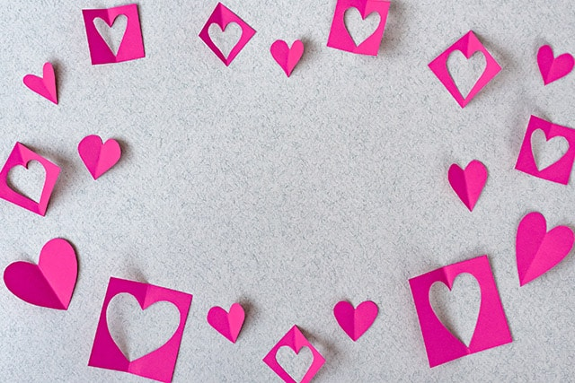 Pink paper hearts and negative-space papers on grey textured background