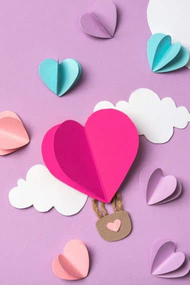 colorful paper hearts and clouds around heart shaped paper hot air balloon on purple background