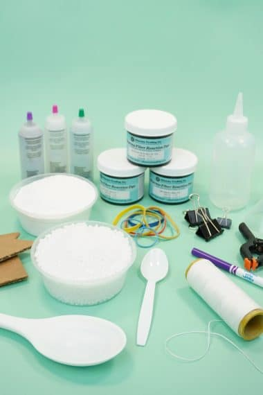 Assorted tie-dye supplies and dye bottles on mint green background