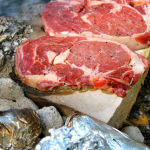 cooking steaks on campfire rocks