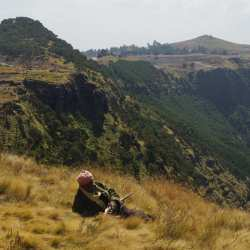 This photo shows an off-duty armed guard relaxing in the Simien Mountains, Ethiopia