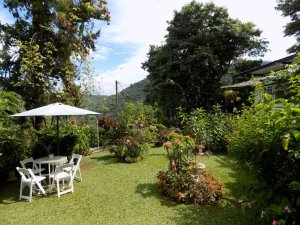 This photo shows a view of the garden at Yerette with a white table and chairs shaded with a parasol and lots of colourful plants and flowers.