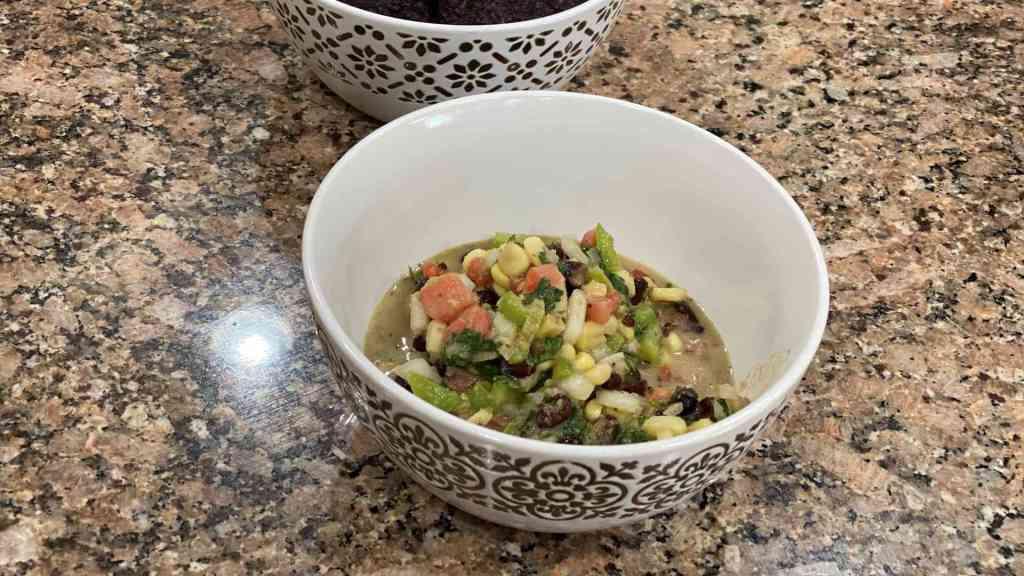 black bean salsa with corn, cilantro, onion, tomato, jalapeno, lime juice, and vinagrete in a bowl.