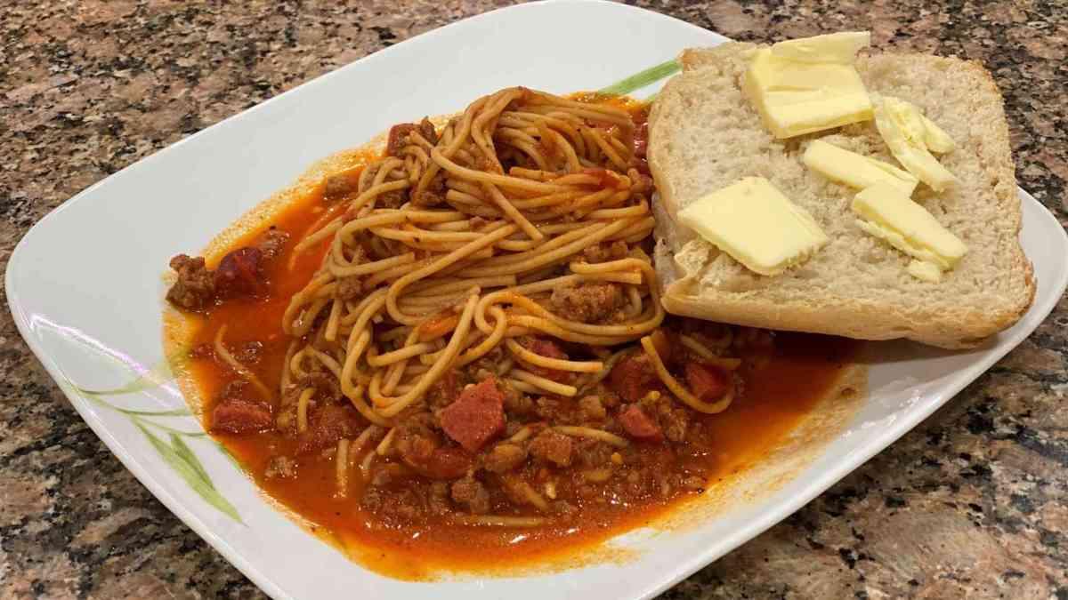 sweet filipino spaghetti with french bread, hotdog, and sausage.
