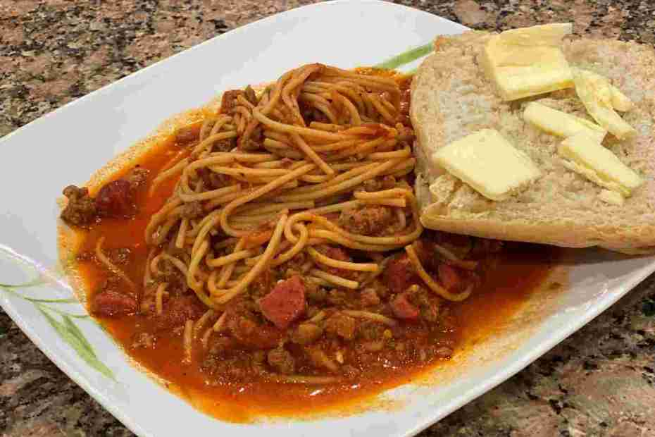 sweet filipino spaghetti with french bread, hotdog, and sausage.