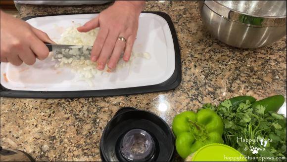man chopping vegetables for black bean salsa recipe
