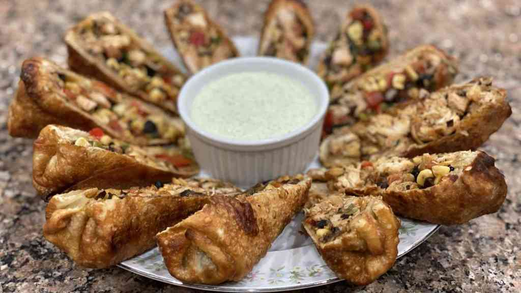 Southwest egg rolls on a plate with cucumber aioli sauce