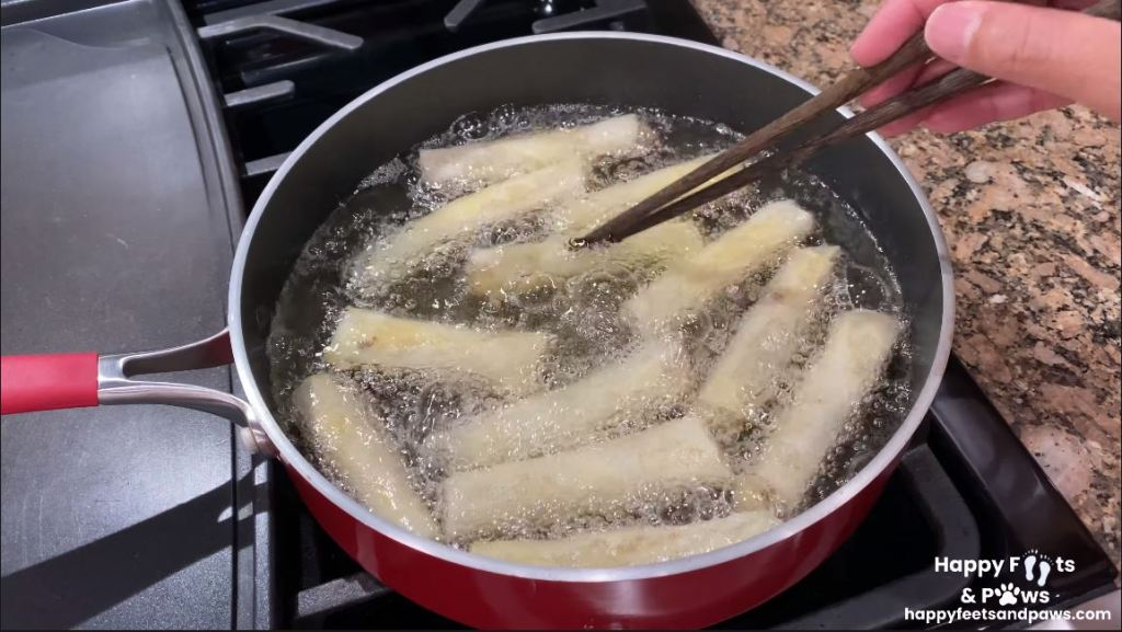 Banana Rum Rolls frying in oil on a stove in a pot