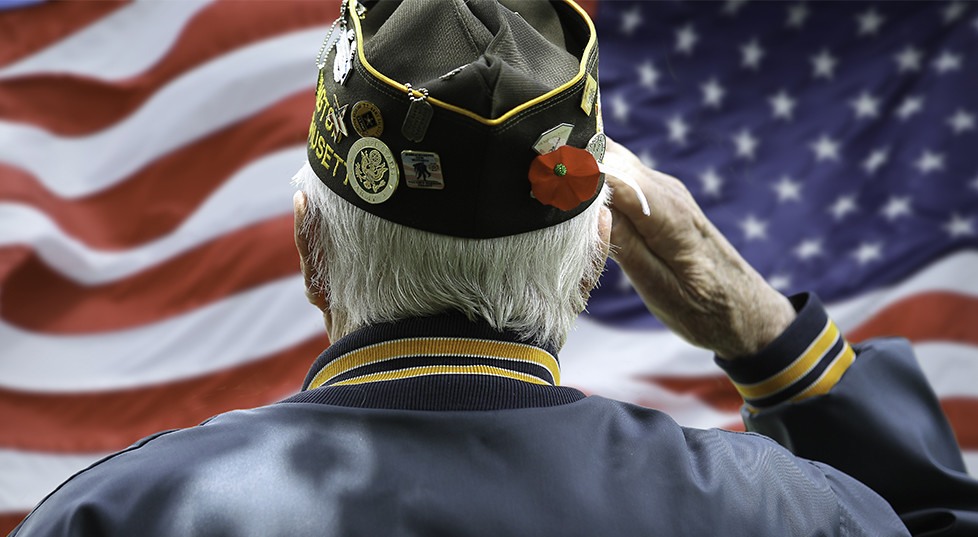war veteran standing in front of American flag