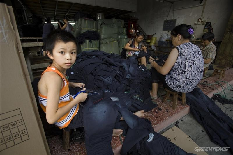 A young boy is working with his parents at a small jeans workshop in Dadun Village in Xintang, Zengcheng. He earns 0.15 yuan for snipping loose thread ends off one pair of jeans; in one day he can do about 200 pairs. In Xintang, where the economy is centered around textile production, Greenpeace has found high levels of industrial pollution and has documented the effects on the community.