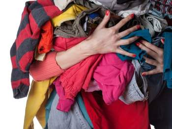 woman holding a pile of clothes to donate after decluttering her closet