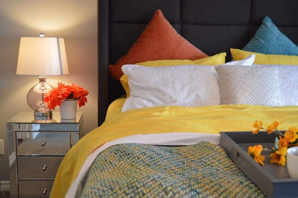 A bedroom with a bed that has orange, yellow, white and blue pillows, a nightstand with orange flowers, and a decorative tray at the end of the bed.