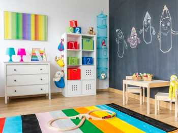 Clutter-free kids' room. View of child room with colorful rug and blackboard wall
