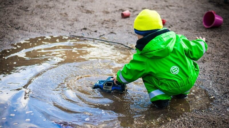 Child playing with a truck in a mud puddle.