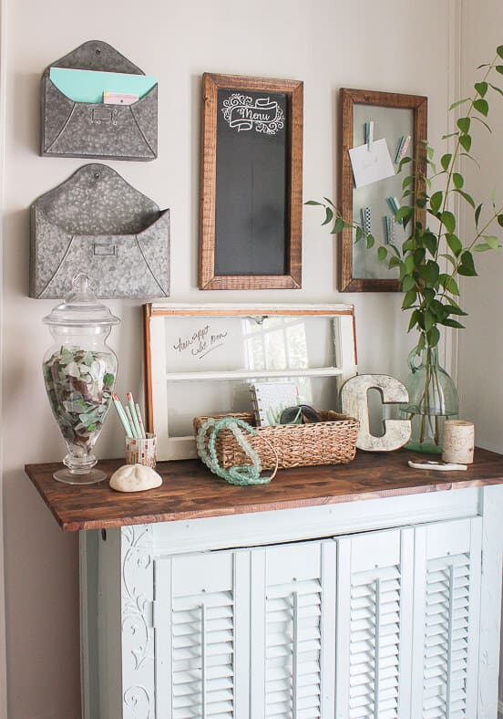Coastal farmhouse command center with giant, silver metal envelopes hanging on the wall.