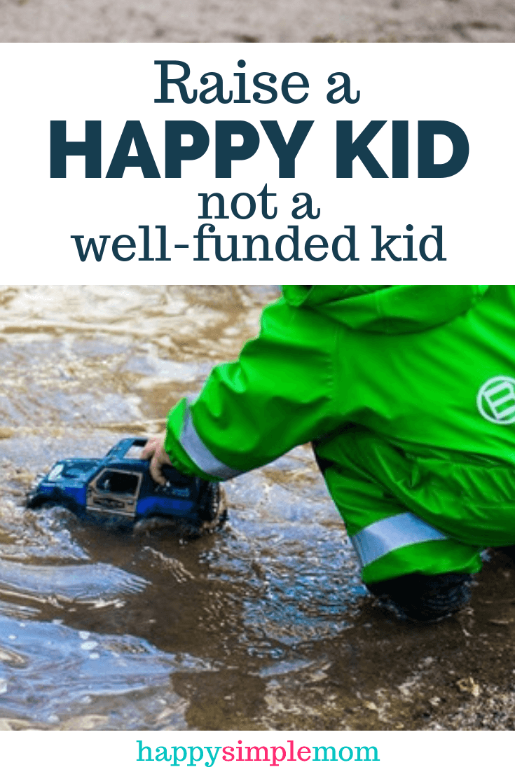Happy kid playing in a mud puddle