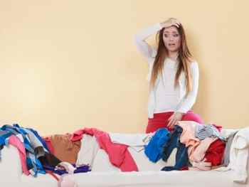 Stressed woman declutterning clothes