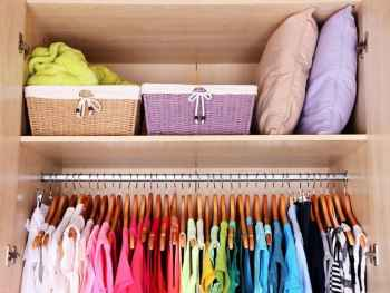 Colorful clothes in a closet with organized baskets.