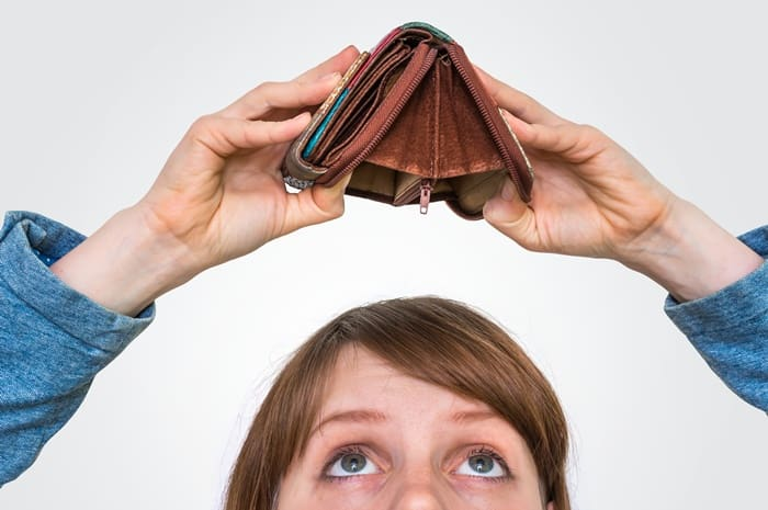 woman looking up at empty wallet