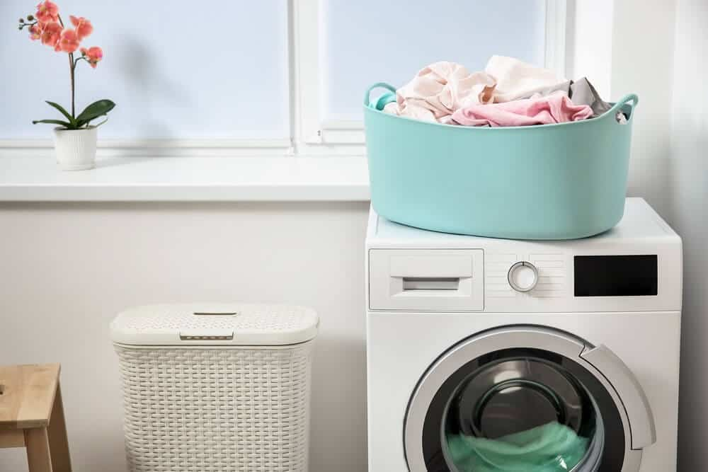 laundry basket with clothes setting on top of a dryer