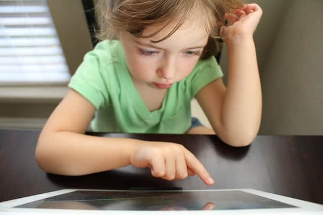 little girl doing online learning on a touchscreen computer