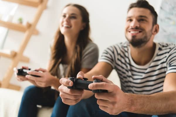 A couple playing video games, another idea for date night at home.