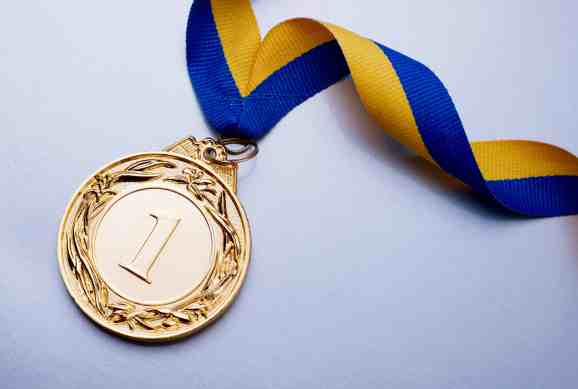 A first place medal on the end of a ribbon that goes around one's neck.