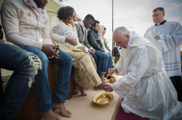 Pope kissing refugees feet