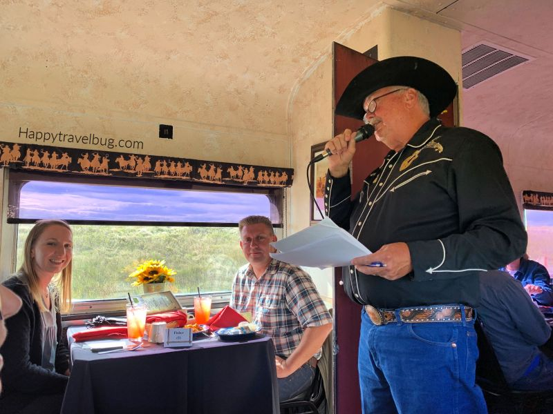 Cowboy on a train talking into a microphone