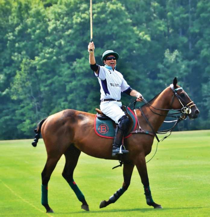Polo Baez raises his mallet to signal the umpire of a foul. Polo has been playing with Mason Lampton for thirty years. He is an accomplished horseman, trainer, and a certified polo instructor. He encompasses the spirit of Bliss Polo. (Photo courtesy of Gayle Donlon Wolf)