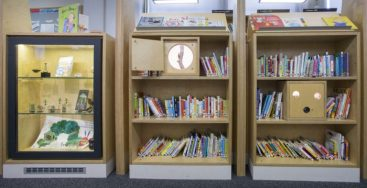 A view of book shelves and a special display area of the story place, which features changing displays based on popular books