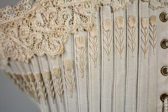 A close-up shot of a corset from the Symington Collection, featuring lace and embroidery