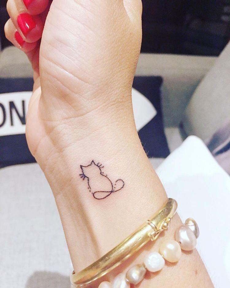 Tatuaje de mujer en la muñeca gato silueta