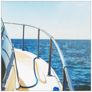 Metal railing on the bow of a boat against calm blue waters and bright blue sky