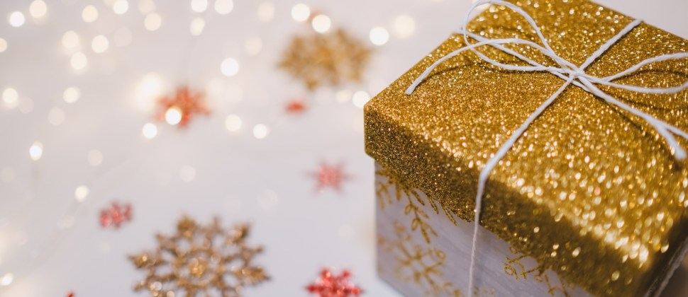 Square box gift with gold top on a white table with gold and red sparkly snowflakes